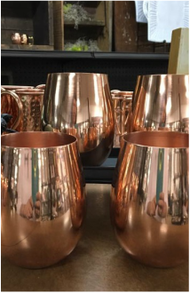 Assortment of copper cups with reflection on them.