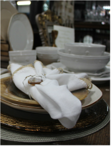 Close up of white and gold china plate with napkin placed over.