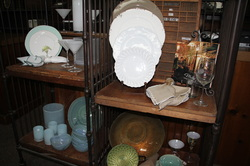 Crop photo of white china on a shelf with other china assortment around it.